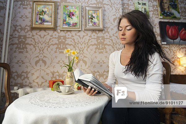 Beautiful young woman reading book in cafe
