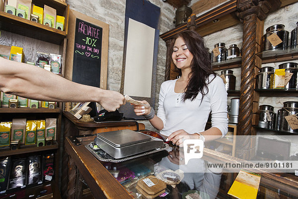 nehmen  lächeln  Geld  Laden  Kunde  jung  Verkäufer  Tee