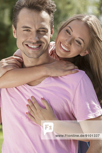 Portrait of smiling young man being embrace by woman in park