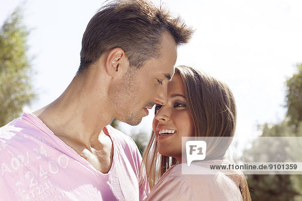 Loving young couple embracing in park
