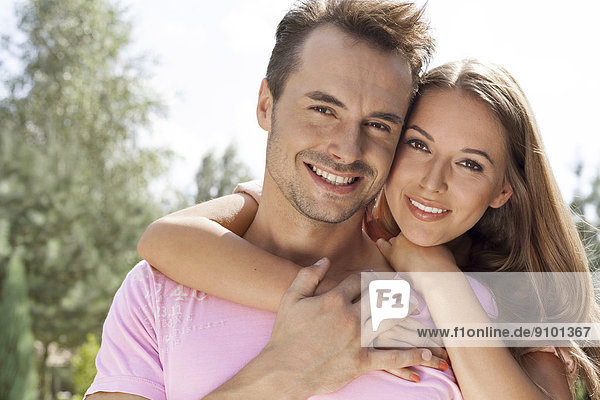 Portrait of beautiful young woman embracing man in park