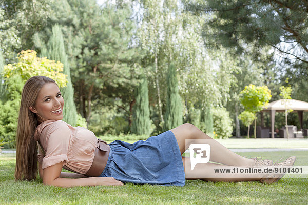 Full length of beautiful young woman reclining on grass in park