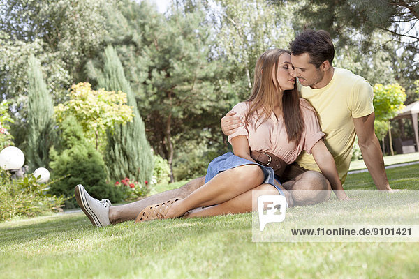 Full length of romantic young couple relaxing in park
