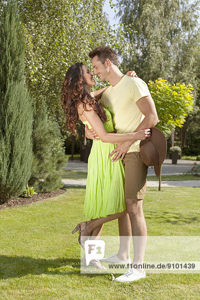 Full length of smiling young couple embracing in park