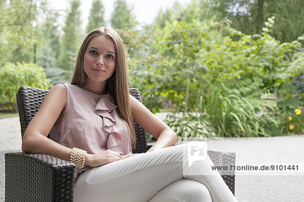 Portrait of beautiful young woman sitting on chair in summer park