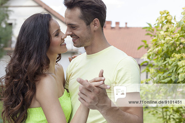 Romantic young couple dancing in park