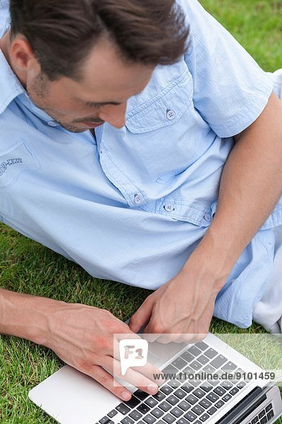 High angle view of young man using laptop in park