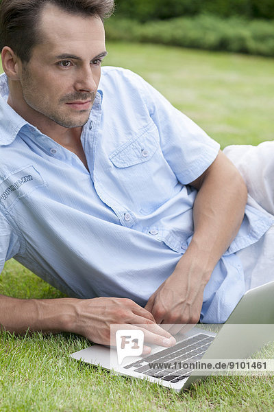 Thoughtful young man with laptop in park