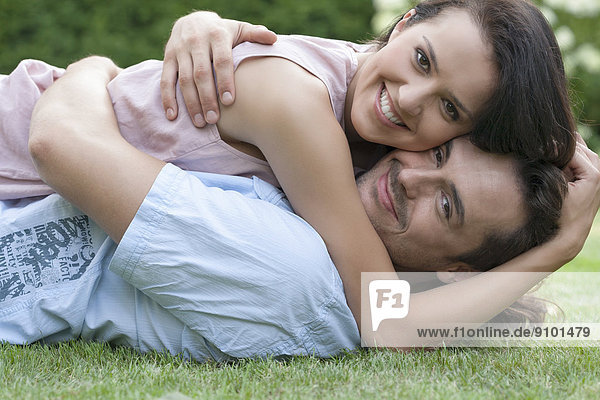 Portrait of smiling young couple embracing while lying in park