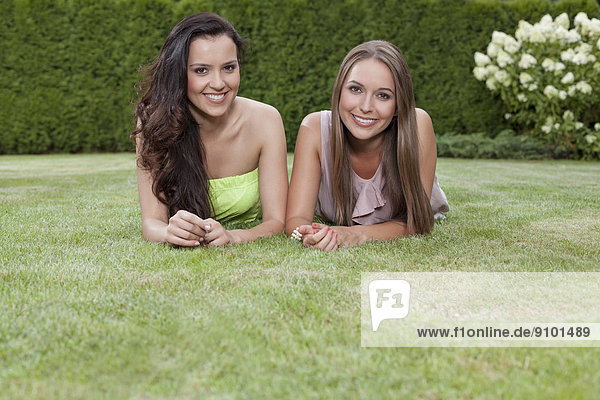 Portrait of beautiful young women with long hair lying in park