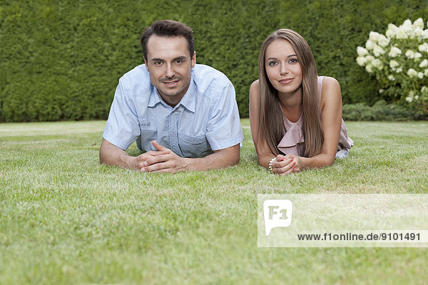 Portrait of happy young couple lying on grass in park