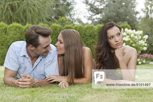 Loving young couple ignoring female friend in park
