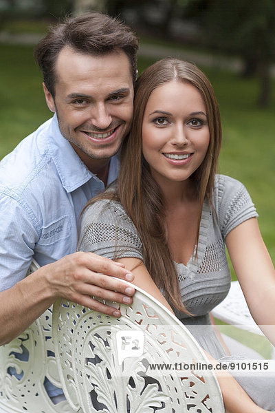 Portrait of loving young couple sitting on chairs in park