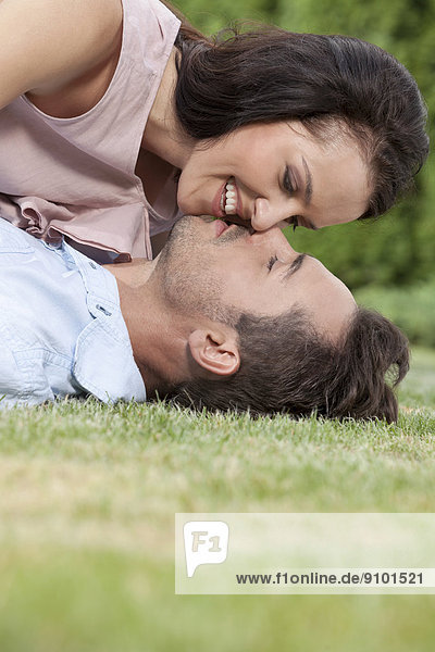 Side view of loving young couple about to kiss in park