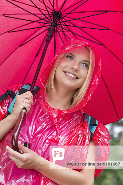 Regenmantel  lächeln  Regenschirm  Schirm  halten  wandern  rot