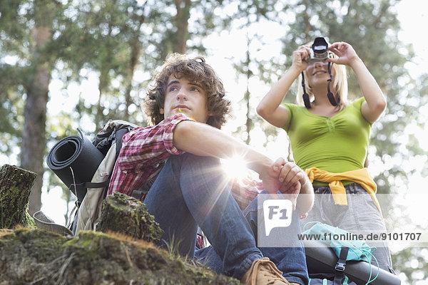 Mann  sehen  Wald  wandern  fotografieren  Fotoapparat  Kamera  blättern  Blick in die Kamera  jung  wegsehen  Reise