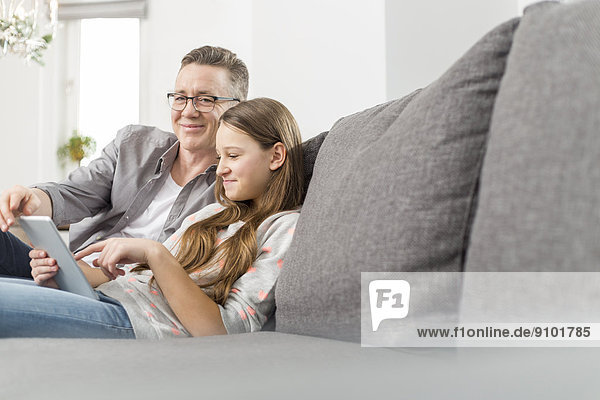 Portrait of smiling father assisting daughter in using digital tablet on sofa at home