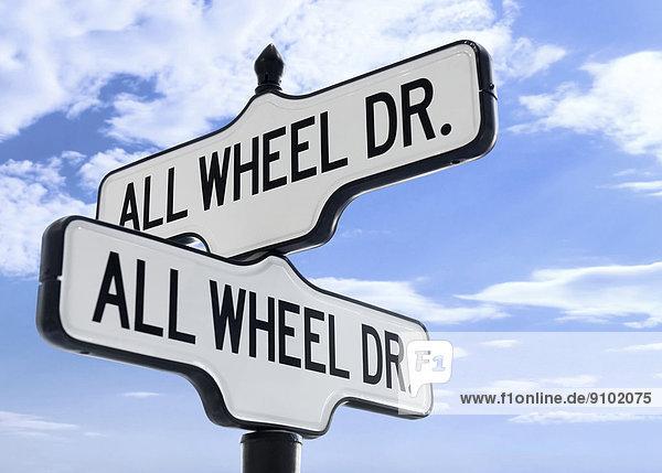 'Zwei Straßenschilder mit dem Namen ''All Wheel Drive''  vor blauem Himmel'