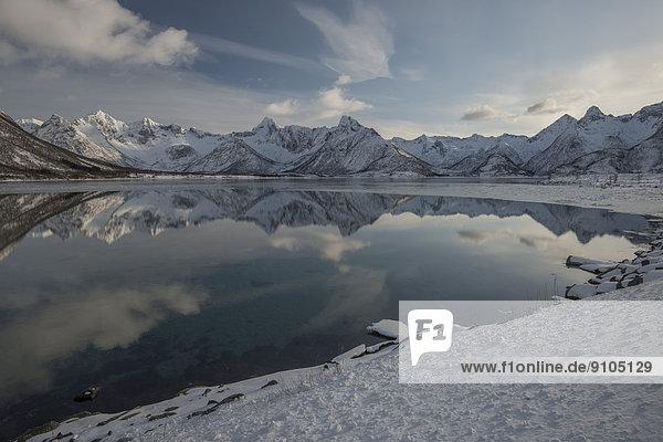 Verschneite Bergkette spiegelt sich im Wasser  Vågan  Lofoten  Norwegen