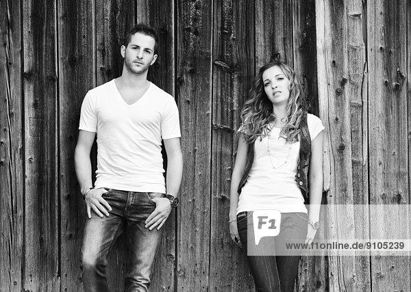 Junger Mann und junge Frau vor Holzwand Junger Mann und junge Frau vor Holzwand