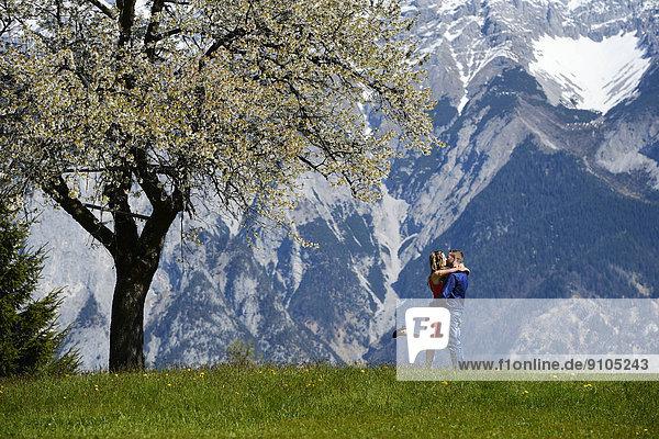 Liebespaar umarmt sich neben einem blühenden Baum im Frühling  hinten Berge  Tirol  Österreich