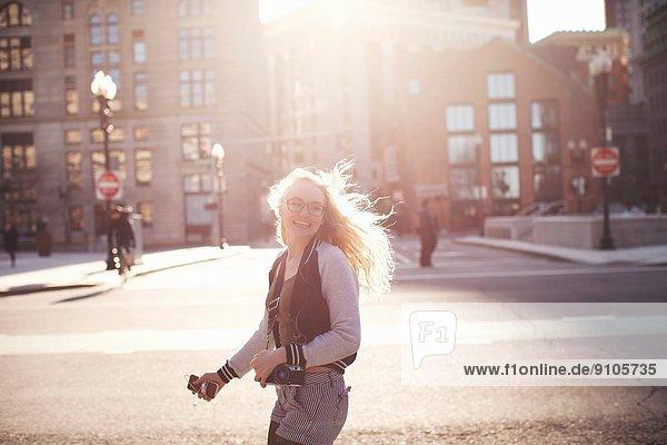 Junge Frau  die in Boston die Straße entlang geht  mit Kamera und Smartphone.