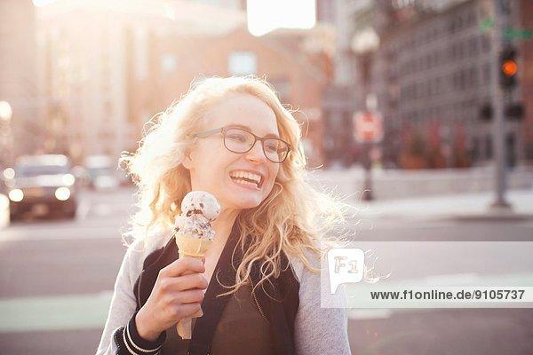 Junge Frau isst Eis auf der Straße