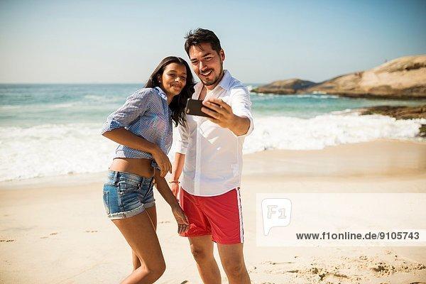 Pärchen nehmen Selfie auf Smartphone  Arpoador Strand  Rio De Janeiro  Brasilien