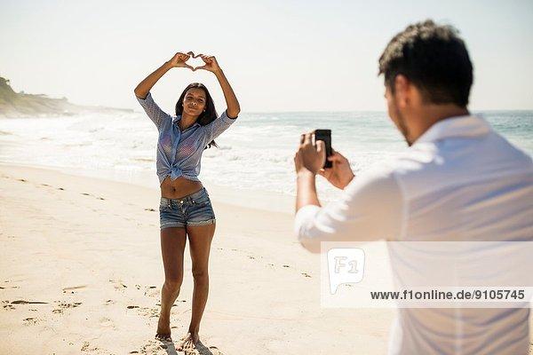 Mid Erwachsene Mann fotografiert Freundin auf Smartphone  Arpoador Strand  Rio De Janeiro  Brasilien