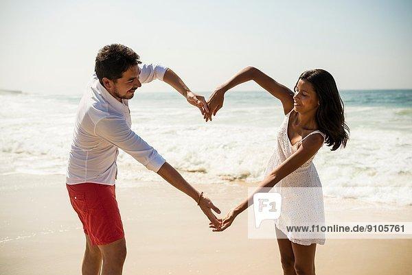 Herzform mit Armen am Strand von Arpoador  Rio De Janeiro  Brasilien