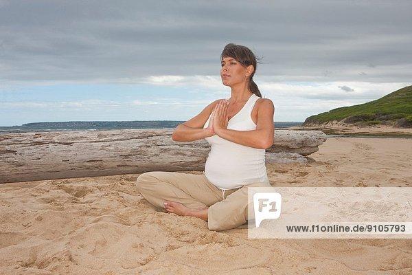 Schwangere mittlere erwachsene Frau  die Yoga am Strand praktiziert.