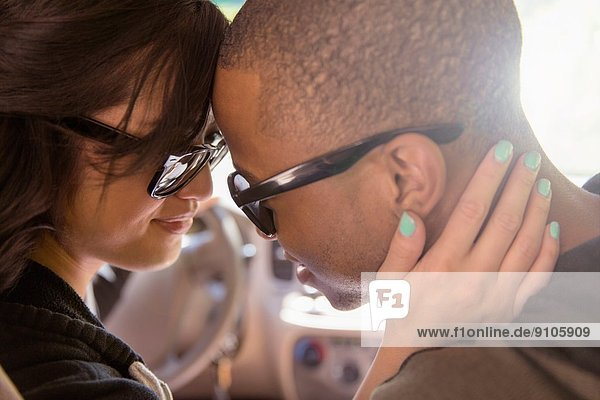 Close up of tender young couple face to face in car