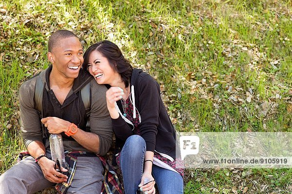 Junges Paar auf Parkgras sitzend