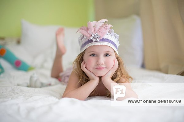 Porträt des jungen Mädchens in Prinzessin-Kopfschmuck auf dem Bett Porträt des jungen Mädchens in Prinzessin-Kopfschmuck auf dem Bett
