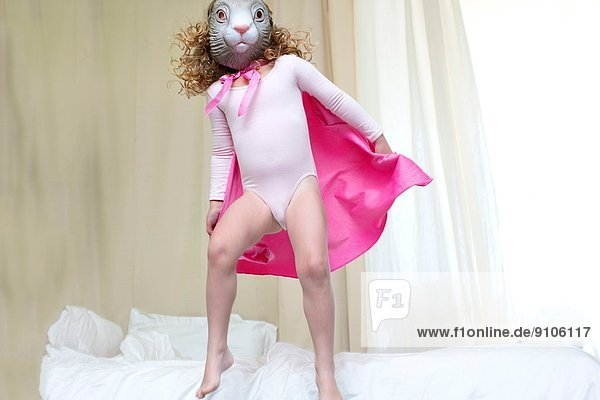 Junges Mädchen verkleidet als Kaninchenprinzessin  die auf dem Bett tanzt. Junges Mädchen verkleidet als Kaninchenprinzessin, die auf dem Bett tanzt.