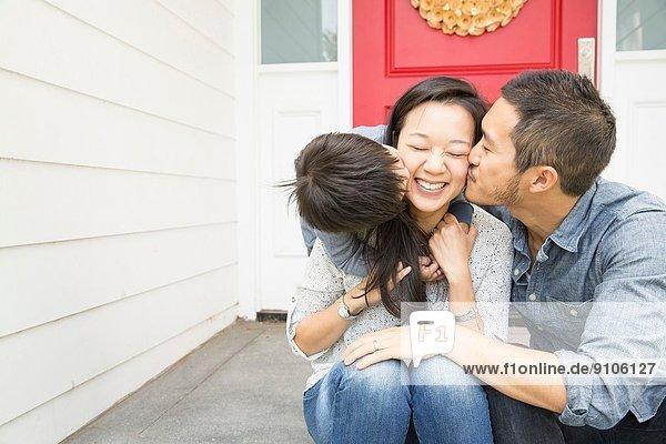 Mittleres erwachsenes Paar mit jungem Sohn auf der Veranda