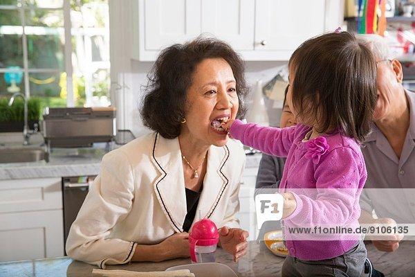 Weibliches Kleinkind füttert Großmutter in der Küche