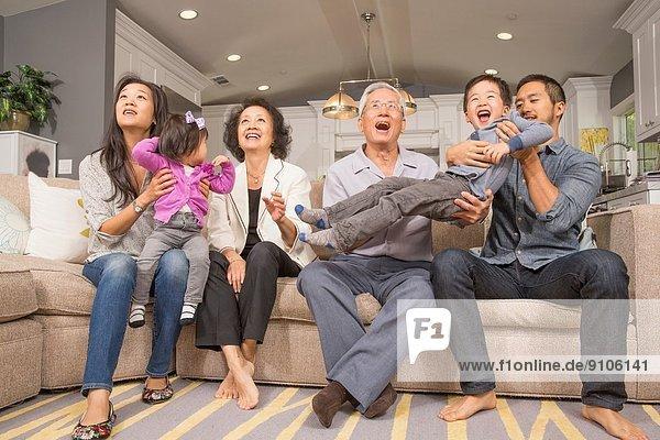 Drei Generationen Familie spielen zusammen auf dem Sofa