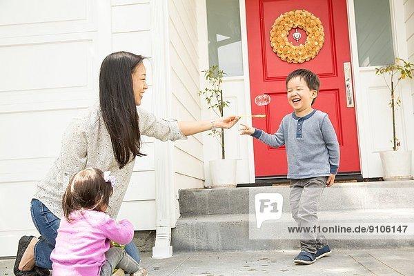 Mittlere erwachsene Frau mit jungem Sohn und Tochter  die Blasen machen.