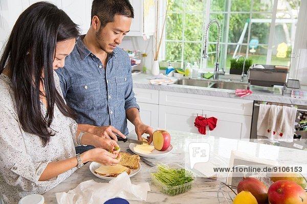Mittleres erwachsenes Pärchen bei der Zubereitung des Sandwiches an der Küchenzeile