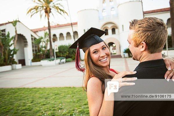 Weibliche Absolventin umarmt Mann