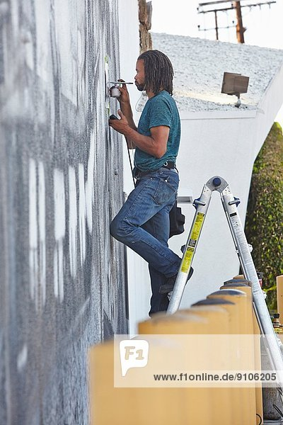Afroamerikanischer Airbrush-Künstler auf Stehleitern Wandmalerei