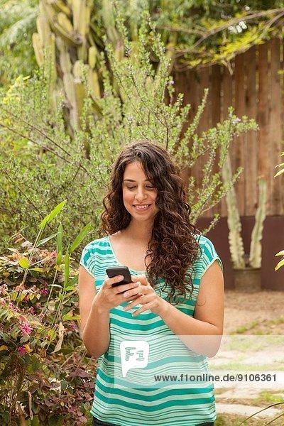 Mädchen im Garten mit Smartphone