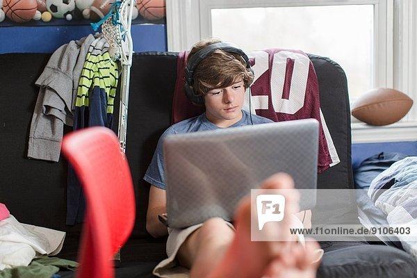 Teenager-Junge sitzt auf Stuhl mit Laptop-Computer