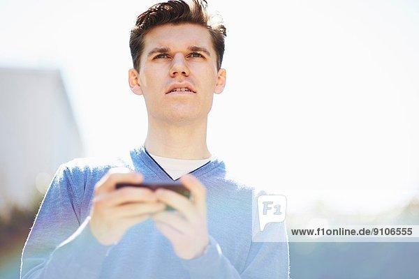Junger Mann mit Smartphone  der wegguckt