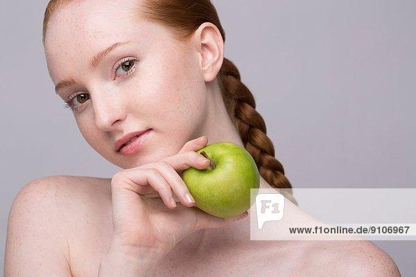 Porträt einer jungen Frau  die einen grünen Apfel hält