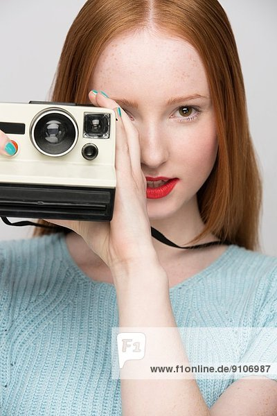 Junge Frau mit Polaroidkamera
