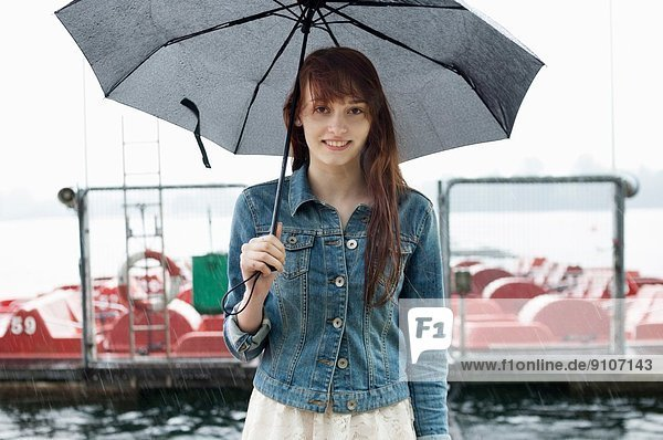 Portrait of young woman by lake with umbrella