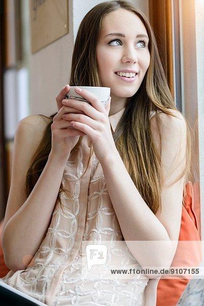 Junge Frau sitzend mit Kaffee im Café