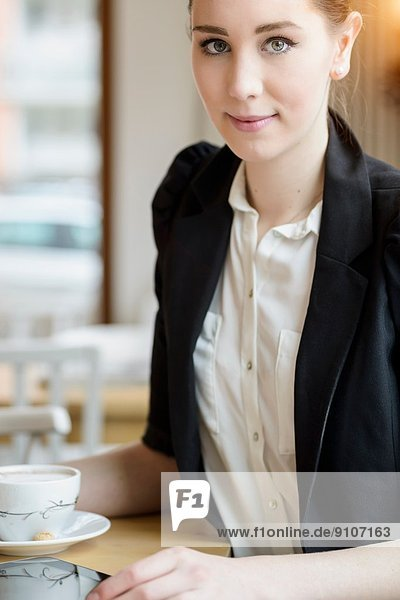 Young businesswoman in cafe having a coffee